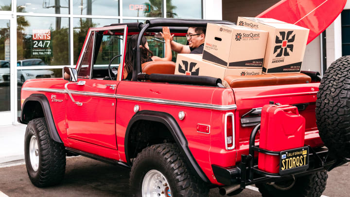 A woman and man high-fiving in a red jeep with moving boxes and a surfboard inside it
