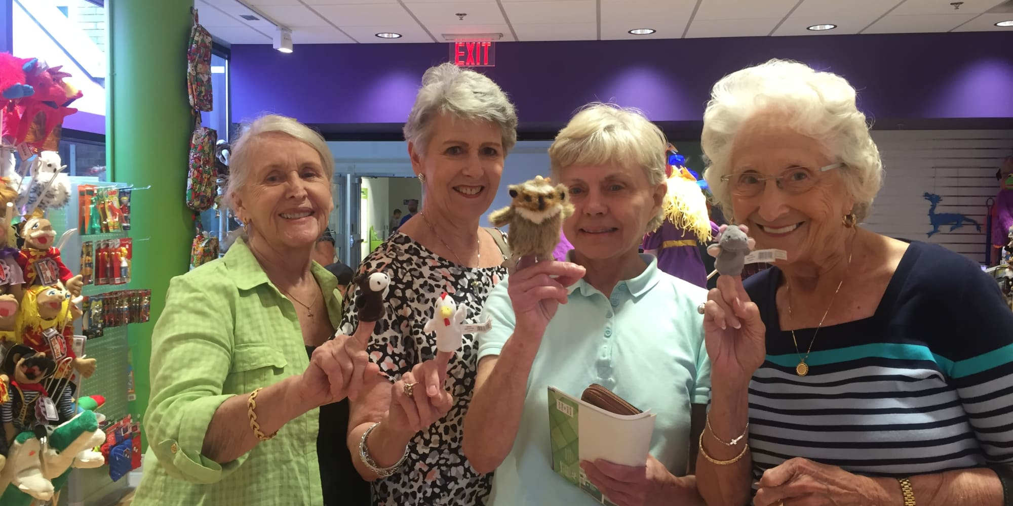 A group of residents from Linwood Estates Gracious Retirement Living in Lawrenceville, Georgia holding finger puppets in a store