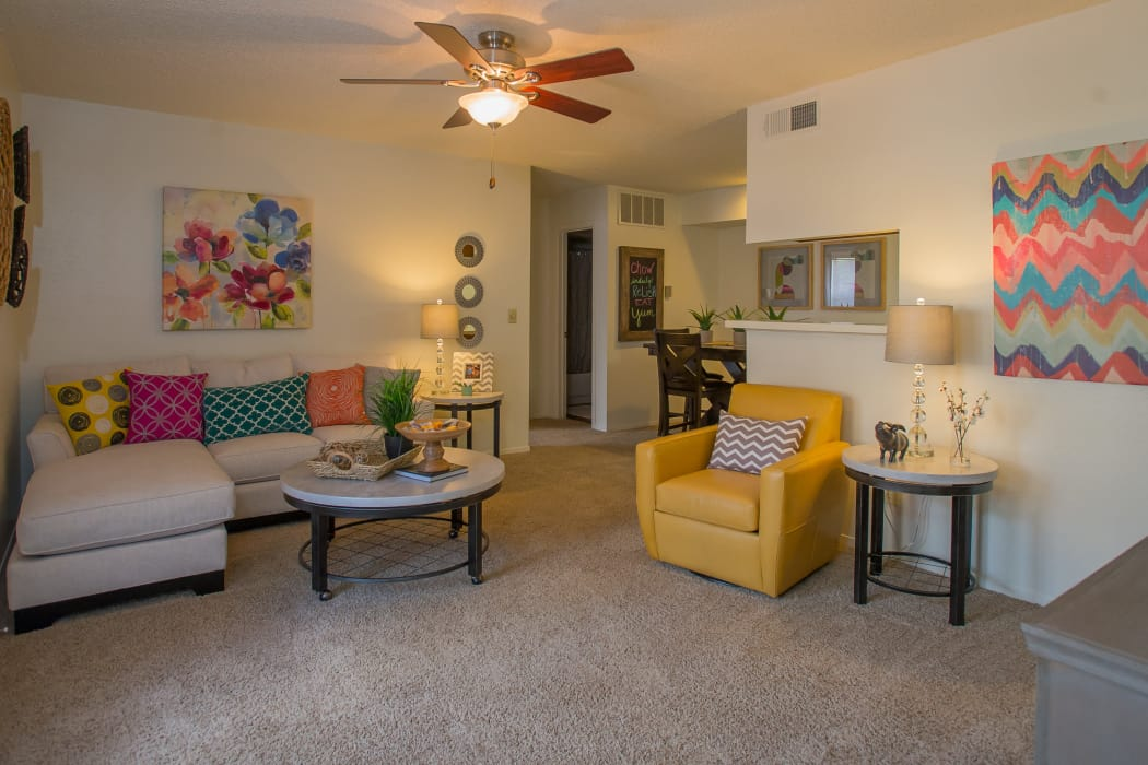 Living room with a ceiling fan and bright decor at Cimarron Trails Apartments in Norman, Oklahoma