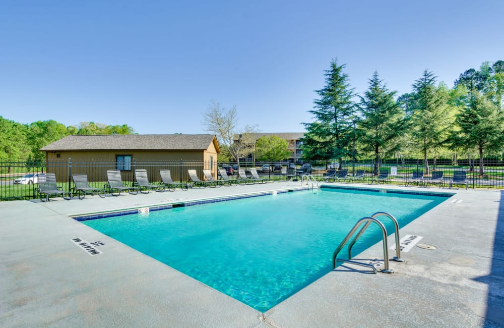 Swimming pool with a large sundeck for sunbathing at Woodbrook Apartment Homes in Monroe, North Carolina