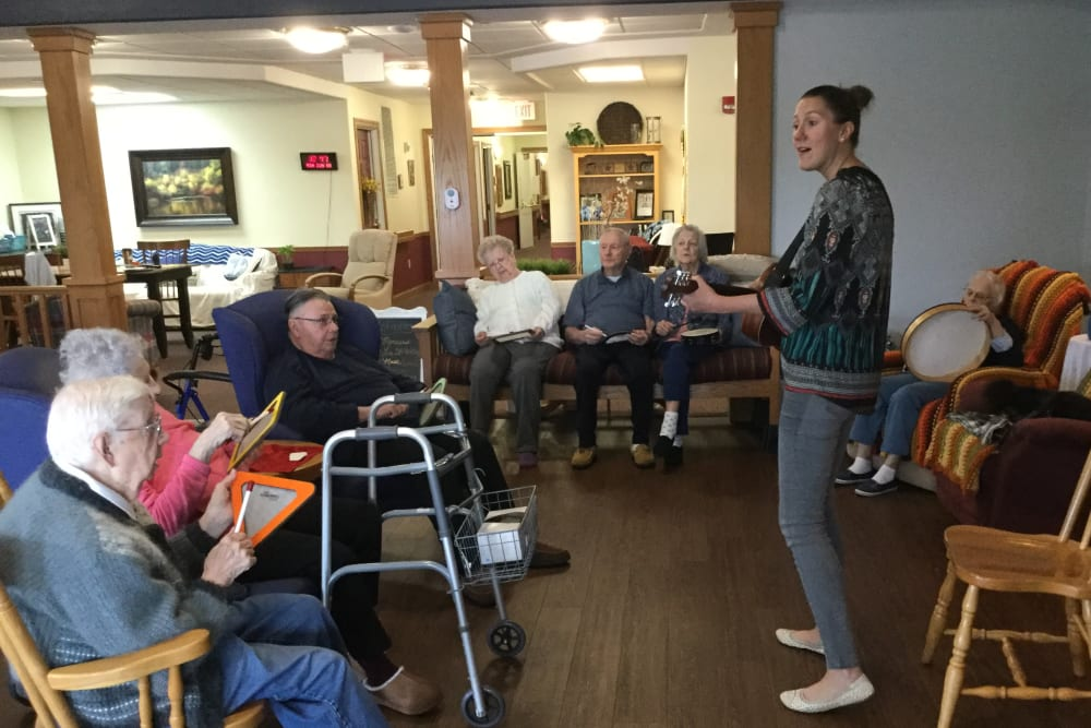 Staff member with residents playing the guitar at Prairie Hills in Independence, Iowa.