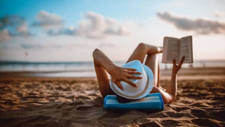 A woman lounging on the beach with a hat on holding a book up as she reads.