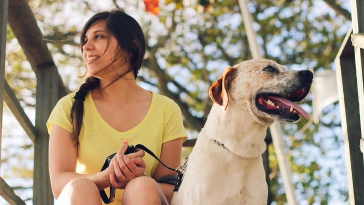 A woman sits with a dog in an outdoor setting in a blog article on our website at Olympus Carrington in Pooler, Georgia.
