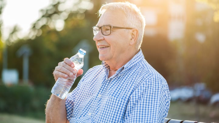 Senior man outdoors drinking water on a beautiful day {{location_name}} in {{location_city}}, {{location_state_name}}