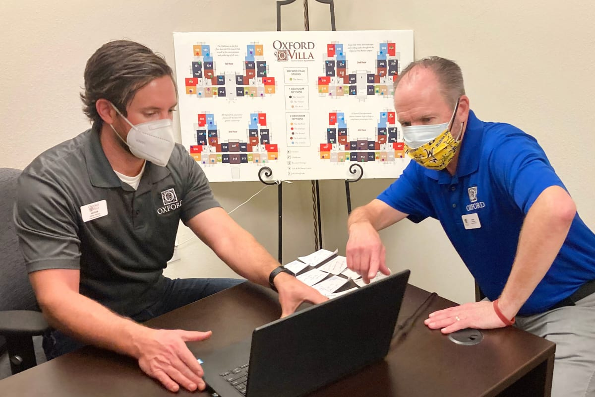 Two oxford employees with face masks on talking behind a computer screen at a Oxford Senior Living location
