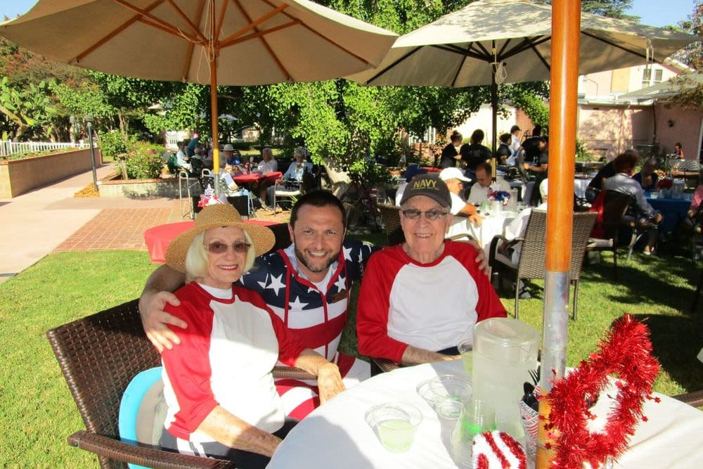 Two residents and a caretaker outside for the Independence Day barbecue at Gables of Ojai in Ojai, California