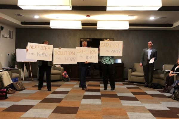 Employees of Discovery Senior Living holding signs at the Texas sales summit in Bonita Springs, Florida