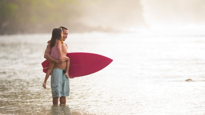 Man standing in shallow ocean water holding a young child in one arm and a surfboard in the other