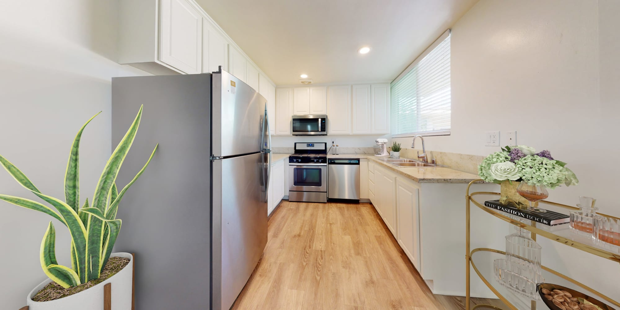 Kitchen with stainless steel appliances and plank flooring in a two-bedroom apartment home at Sunset Barrington Gardens in Los Angeles, California