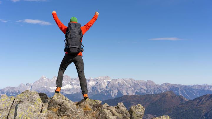 Person stands atop a rocky ridge with hands in the air while looking out over mountains