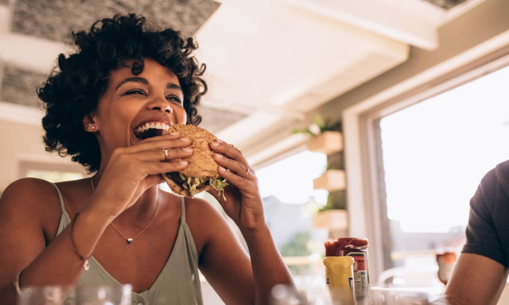 Resident diving into a freshly made burger at her favorite restaurant near Parkwood in Lancaster, California