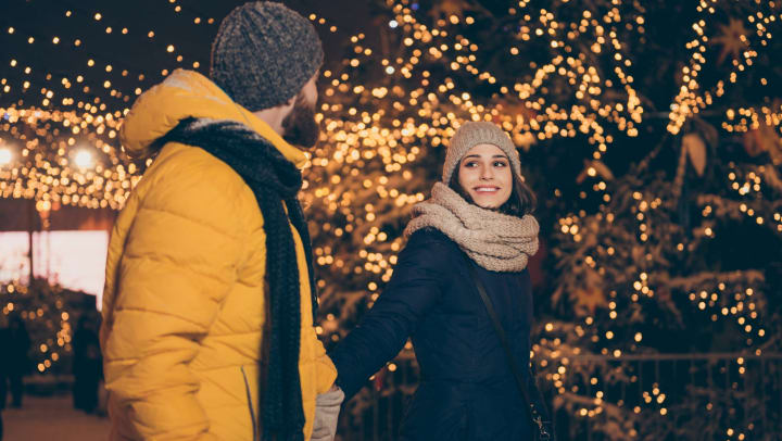A young couple holding hands walking together with holiday lights in the background