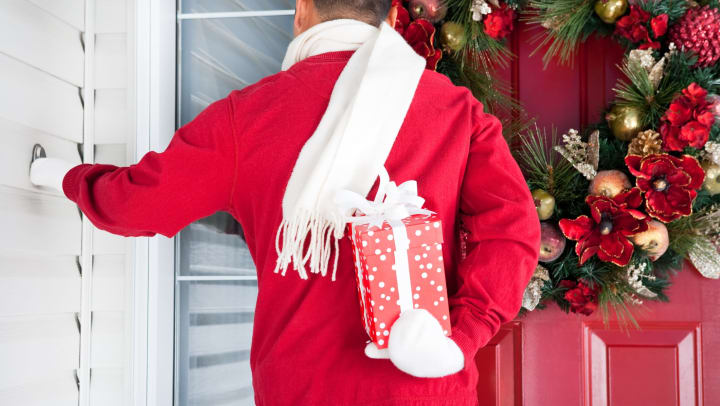 Man standing outside a festive door with a wrapped gift behind his back