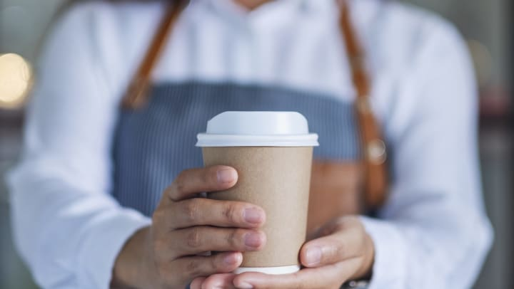 Barista holding out a cup of to go coffee