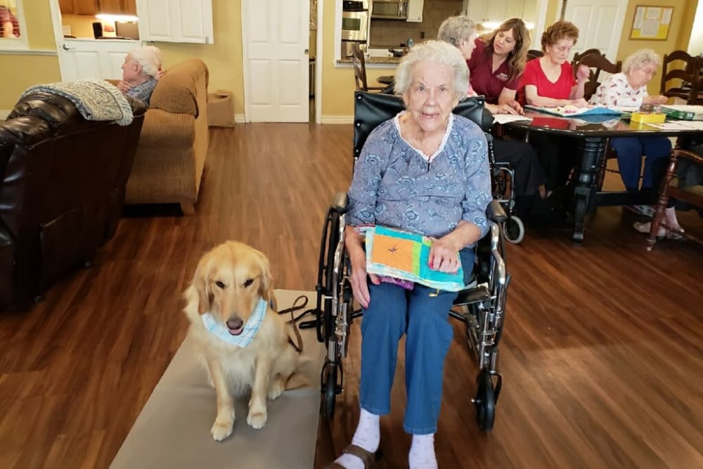 A resident with a therapy dog at Autumn Grove Cottage at Katy in Katy, Texas