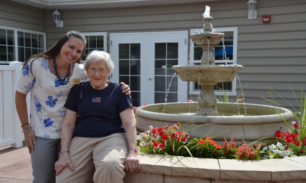 A resident and caretaker next to a fountain at Heritage Green Assisted Living in Mechanicsville, Virginia