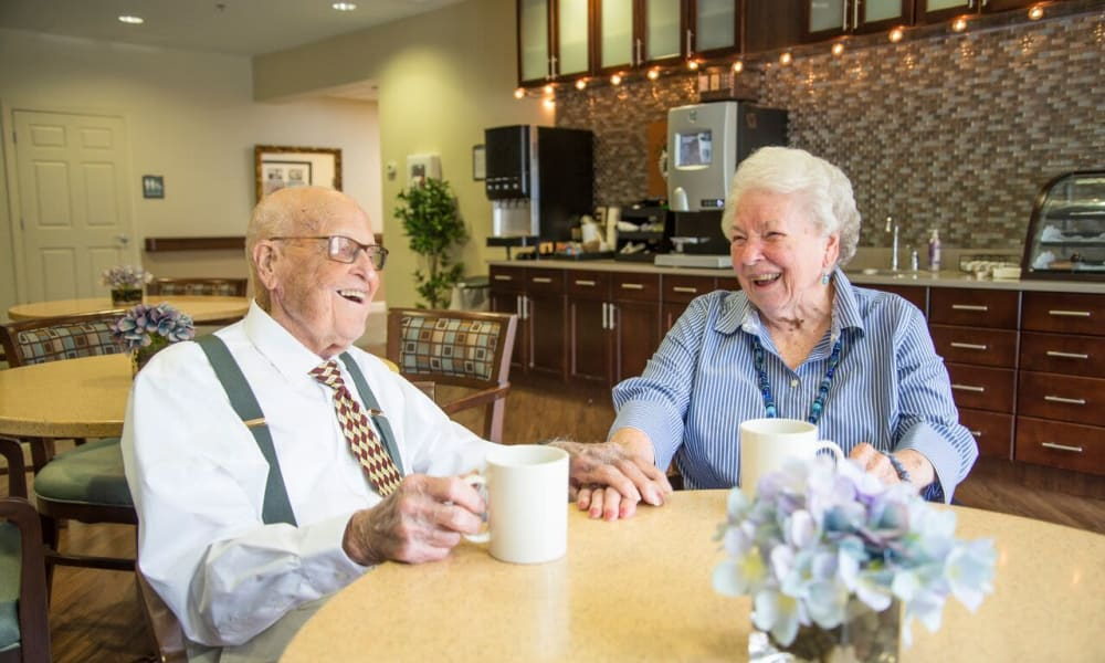 Two laughing residents in the bistro at Heritage Green in Mechanicsville, Virginia