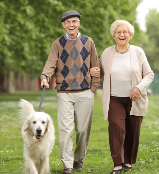Senior couple taking a dog fo a walk at Kenmore Senior Living in Kenmore, Washington