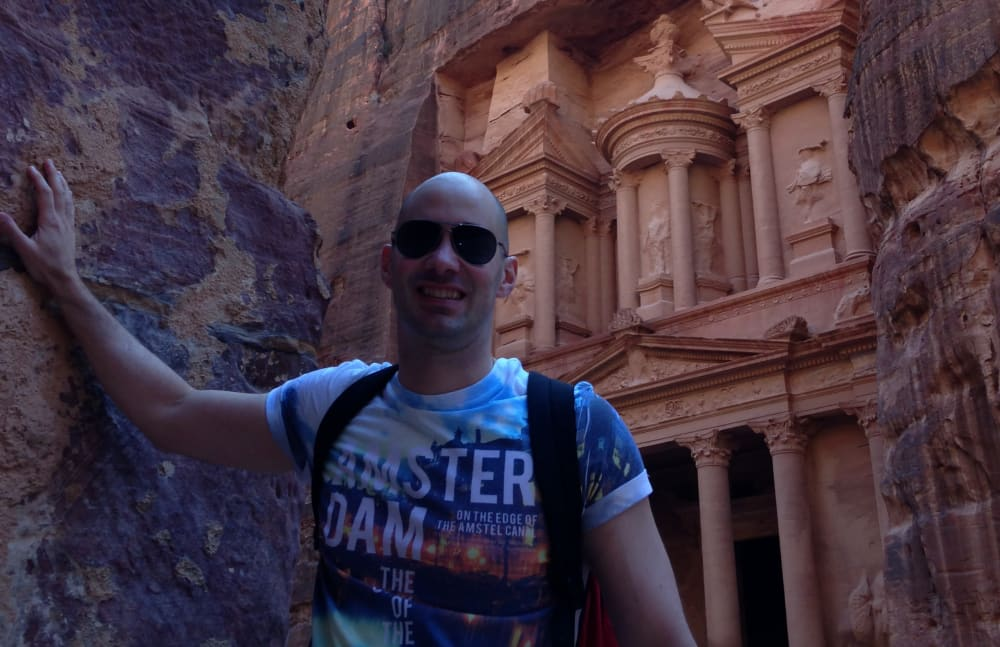 """During one of my many travels abroad, I was fortunate to be able to visit the famous historical and archaeological city of Petra in Jordan's southwestern desert, dating to around 300 B.C.  In this photo, I am standing in front of one of the most elaborate temples in Petra, Al-Khazneh (The Treasury). As with most of the other buildings in this ancient town, this structure was carved out of a sandstone rock face."""