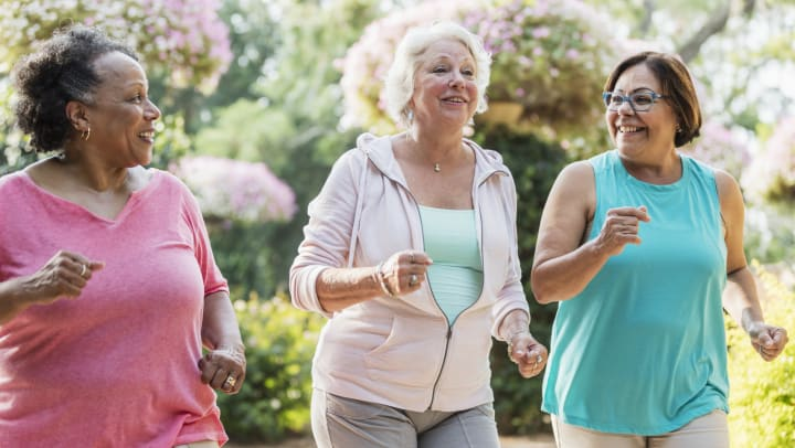 Three women jogging and looking at eachother