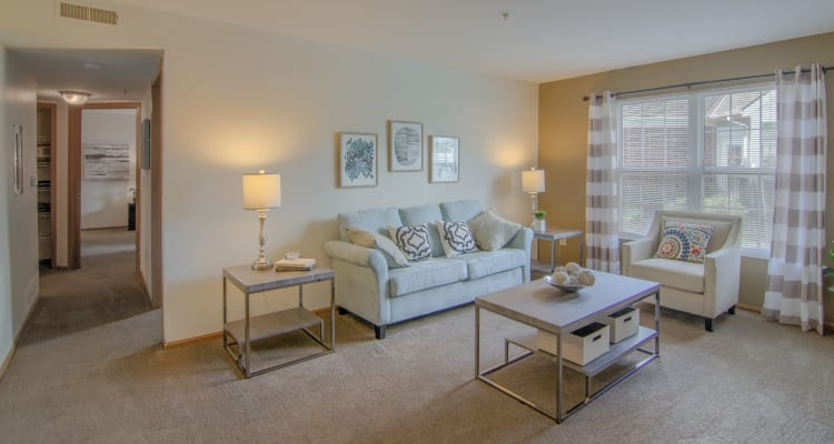 Spacious living room with large windows and natural lighting at Gateway Lakes Apartments in Grove City, Ohio