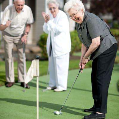 Residents playing golf near at Milestone Retirement Communities