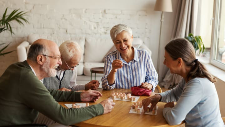 Group of elderly people around a table with game chips and smiles on their faces.