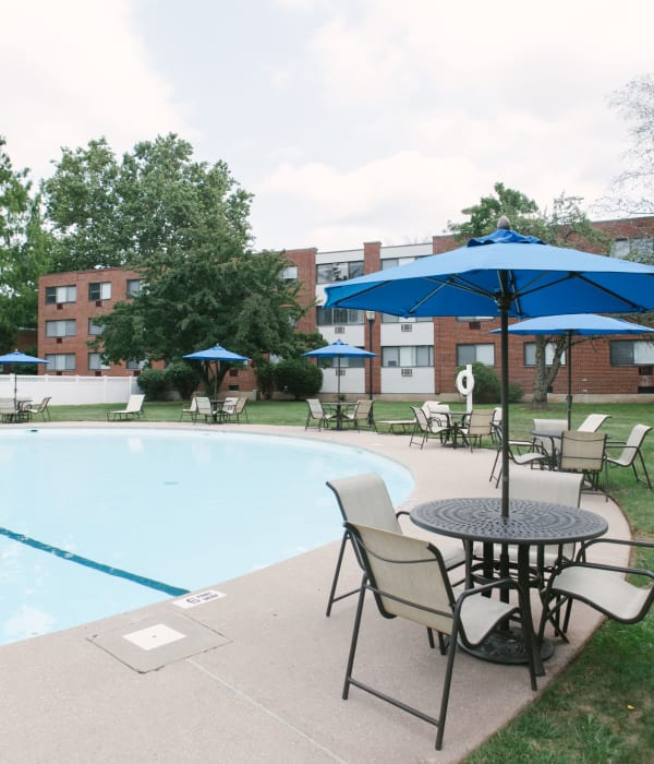 Refreshing pool with umbrellas at each table to get out of the sun at Eagle Rock Apartments at West Hartford in West Hartford, Connecticut