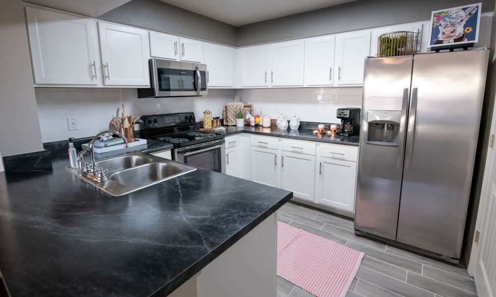 White cabinets and dark counter tops  at Portico at Friars Creek Apartments in Temple, Texas