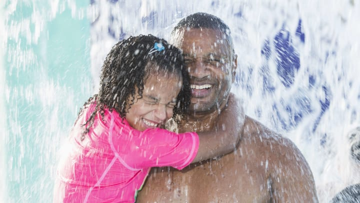 Father and daughter smiling and holding each other as water falls on them at a water park