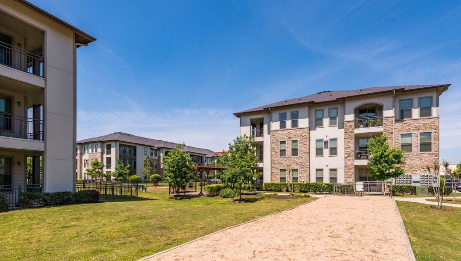 Exterior of Olympus at Waterside Estates with lots of green space in Richmond, Texas