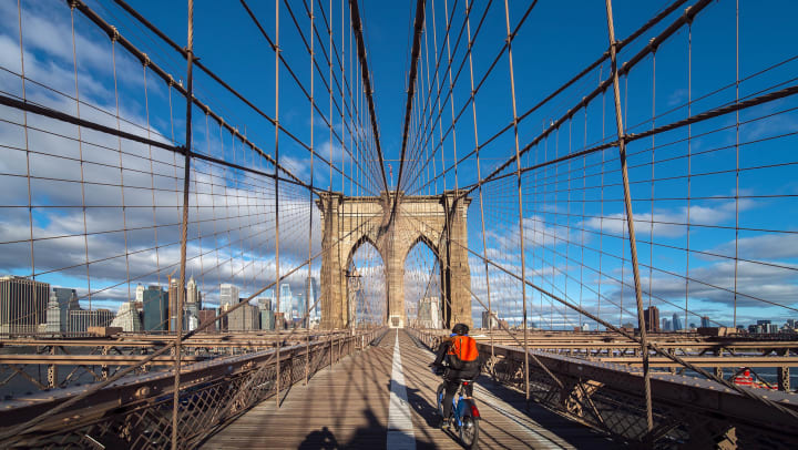 A man riding his bike across the Brooklyn Bridge on a sunny afternoon.