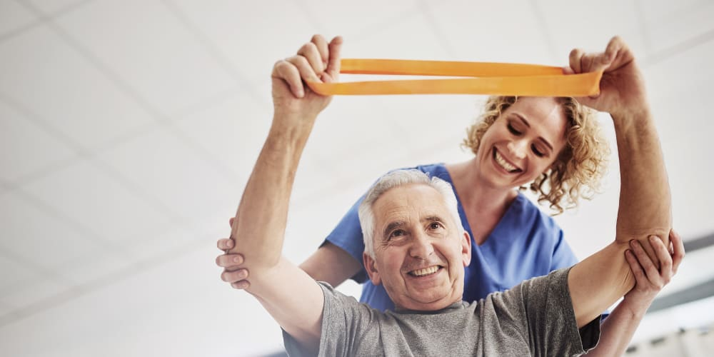 A staff member helping a resident stretch at Careage Home Health in Lakewood, Washington.
