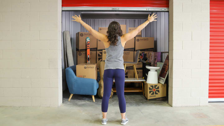 A woman standing with her arms held out in front of a storage unit filled with furniture