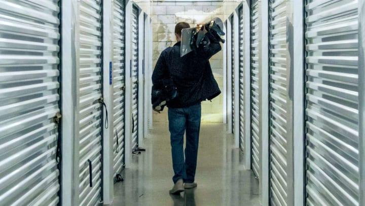 Man holding a snowboard walks through a self storage corridor