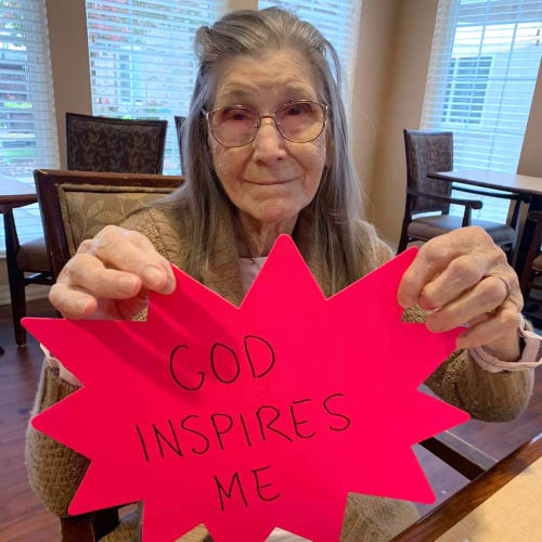 Smiling residents with piece of paper depicting the text 'God inspires me' at Oxford Glen Memory Care at Sachse in Sachse, Texas