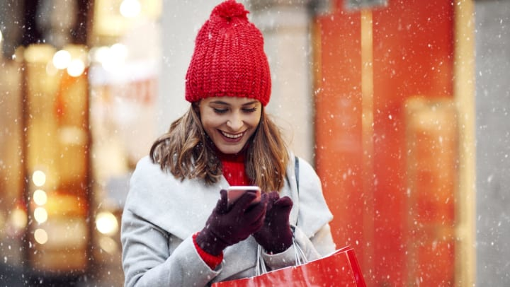 Woman shopper wearing a red hat and gloves in the snow checking her phone outside a department store