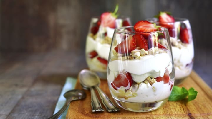 Strawberry desserts in glass cups on a cutting board with spoons set next to them, with a wood background.