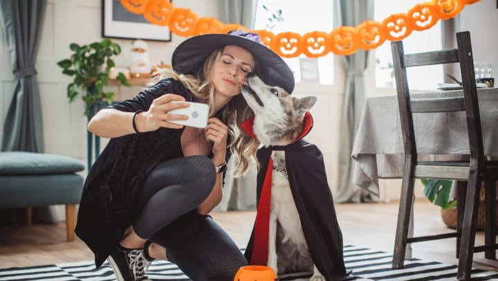 Woman dressed as a witch taking a selfie with her dog dressed as a vampire at Olympus Las Colinas