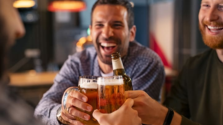 Friends clinking beer beers together at a pub in Tampa