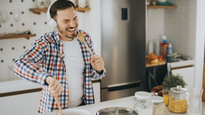 Man mixing food in a pot with a wooden spoon. Singing into a wooden spoon with headphones on. Kitchen background.