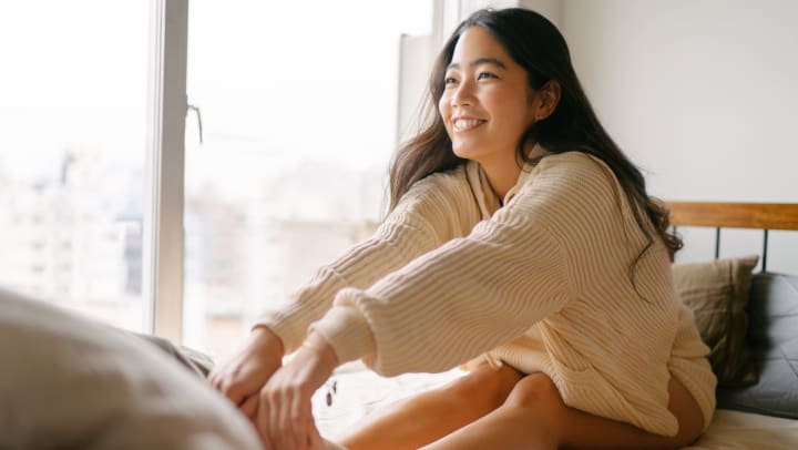 A smiling young woman sitting on a bed and stretching her hands to her toes in a sunlit interior