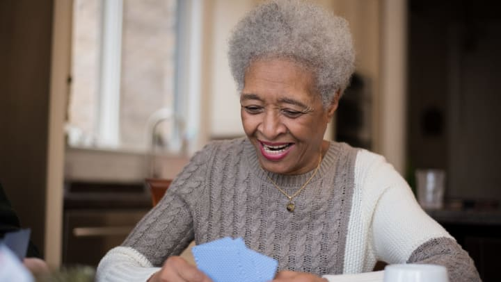 A senior woman smiles as she plays cards with friends.