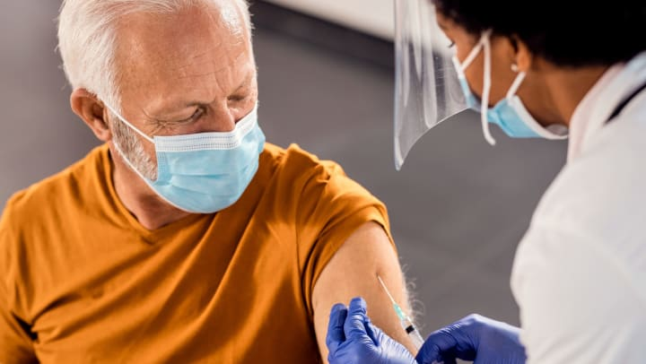 An older man wearing a face mask receiving a vaccine injection in his upper arm.