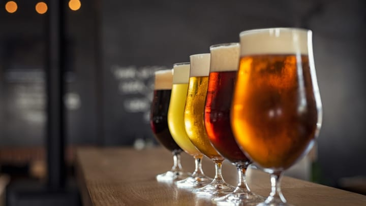 Different colored beers in glasses set on top of a bar with an out of focus industrial background.