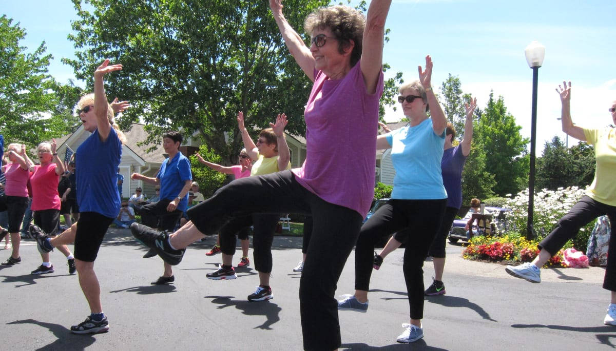Happy residents exercising outside at Touchmark at Fairway Village in Vancouver, Washington