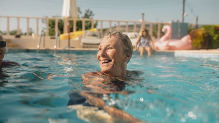 Senior woman swims in a pool while on a vacation near {{location_name}} in {{location_city}}, {{location_state_name}}.
