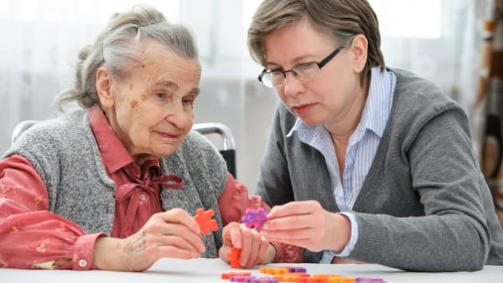 Older woman and younger woman work on puzzle together at {{location_name}} in {{location_city}}, {{location_state_name}}