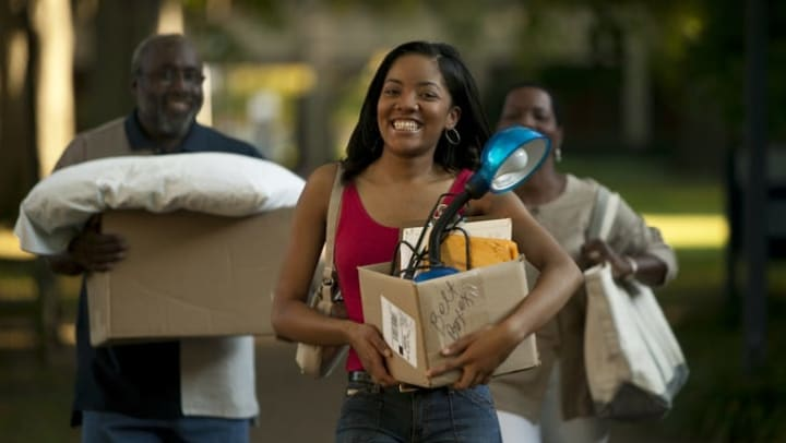 Young woman and older man and woman carrying boxes and bedding to their storage unit at {{location_name}} in {{location_city}}, {{location_state_name}}