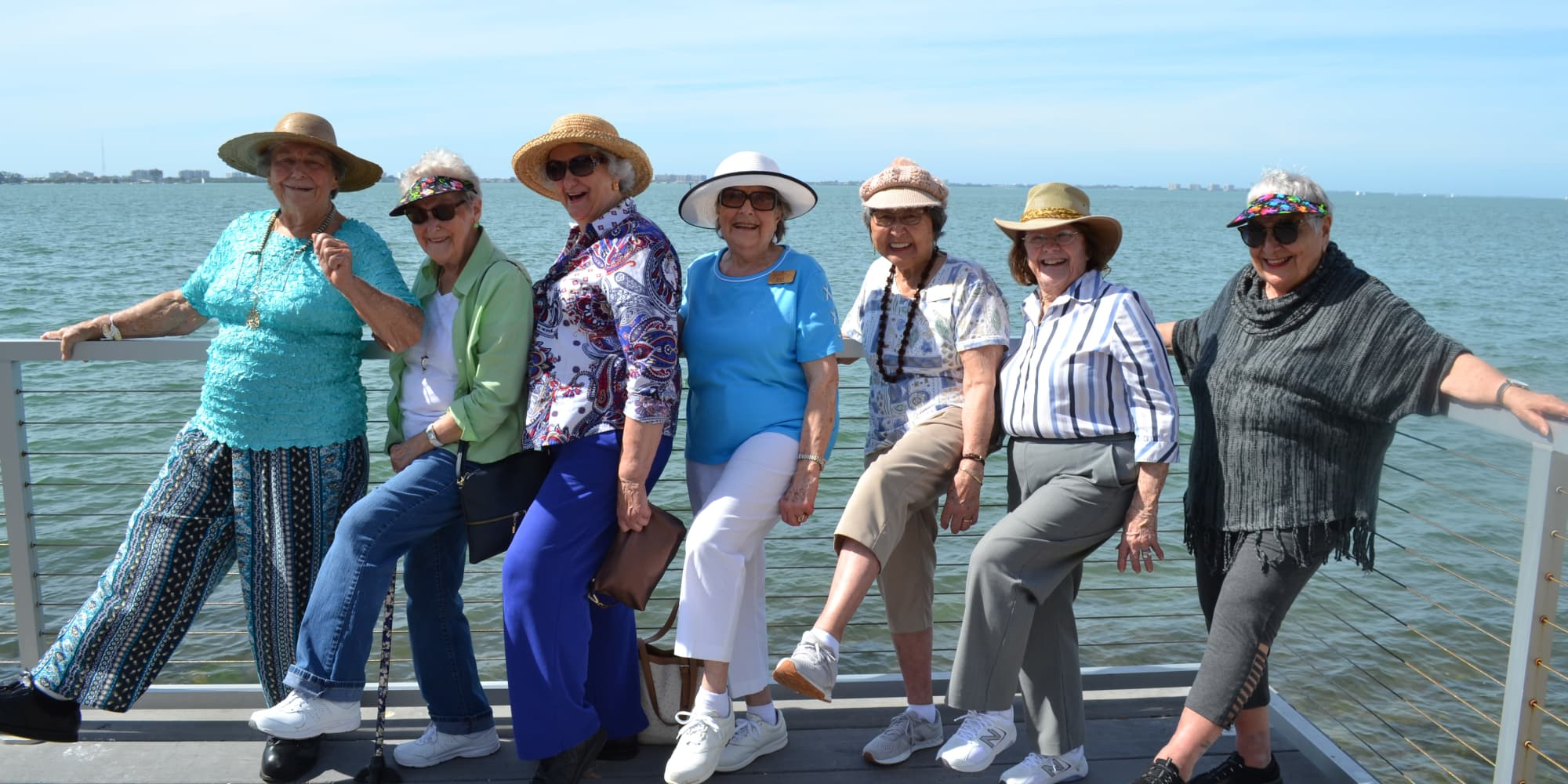 A group of residents from Springwood Landing Gracious Retirement Living in Vancouver, Washington posing for a picture in front of a lake